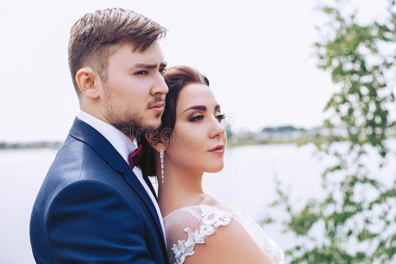 Serious newlyweds stand on the river bank stock photos