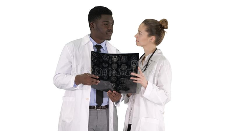 Serious nice woman doctor and afro american doctor study brain x ray on white background. Medium shot. Serious nice women doctor and afro american doctor study royalty free stock photos