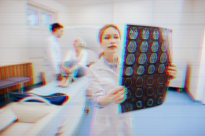 Serious nurse holding MRT results and a patient talking to a doctor stock photo