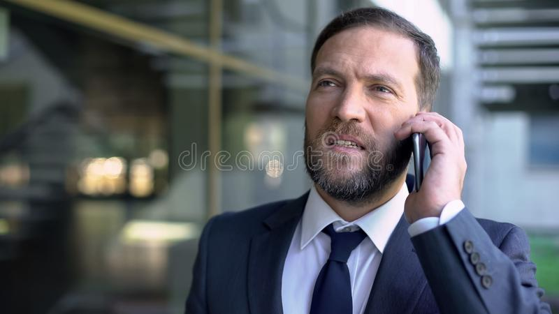 Serious office manager talking on phone, discussing business with partner, work royalty free stock photo