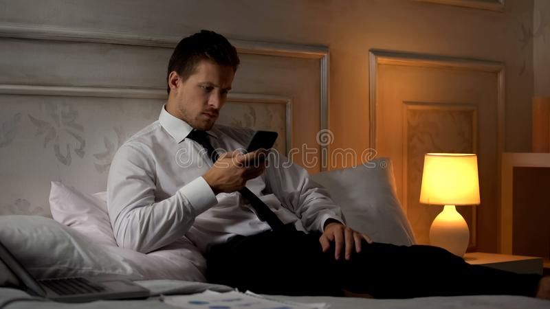 Serious office worker testing new business app, using smartphone at home royalty free stock photography