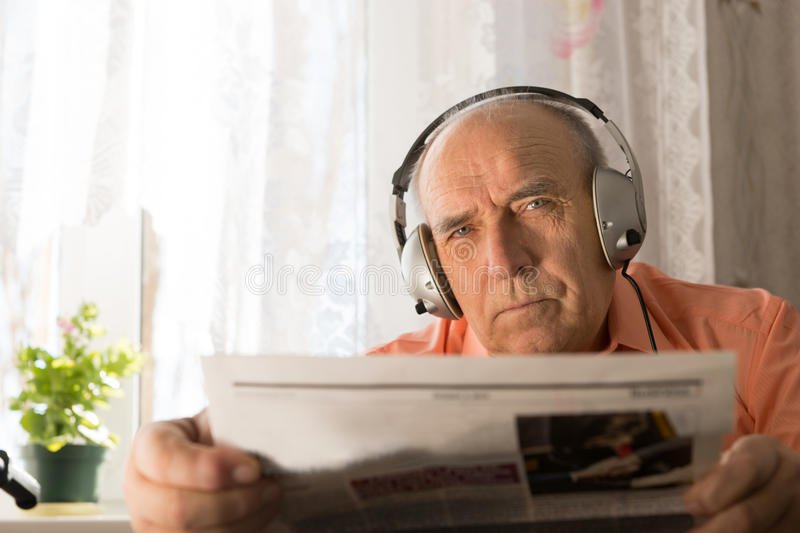 Serious Old Age Man with Headset Holding Newspaper. Close up Serious Old Age Man with Headset Holding Newspaper While Staring at the Camera royalty free stock photos