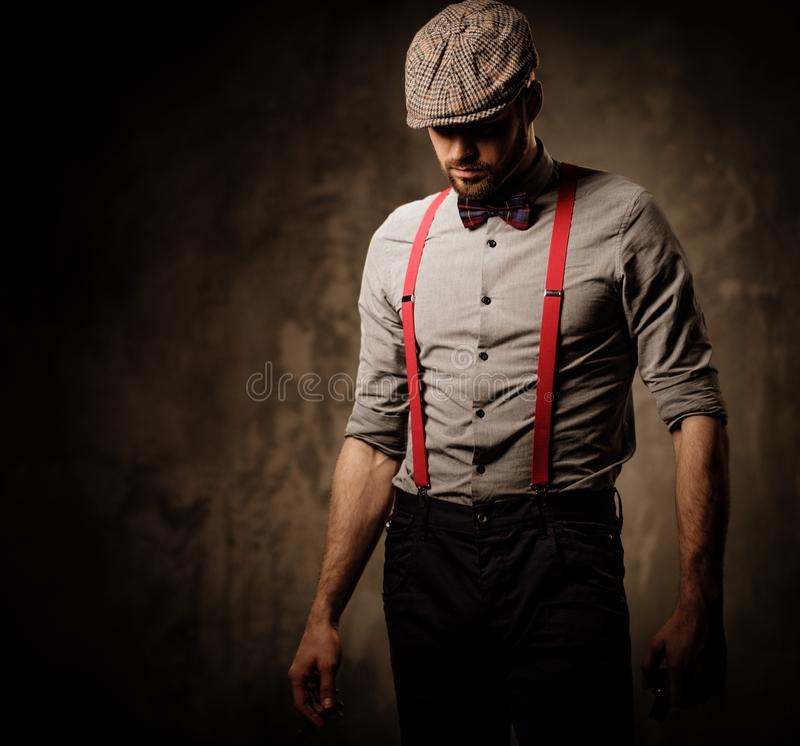 Free Serious Old-fashioned Man In Tweed Hat Wearing Suspenders And Bow Tie, Posing On Dark Background. Royalty Free Stock Image - 69767356