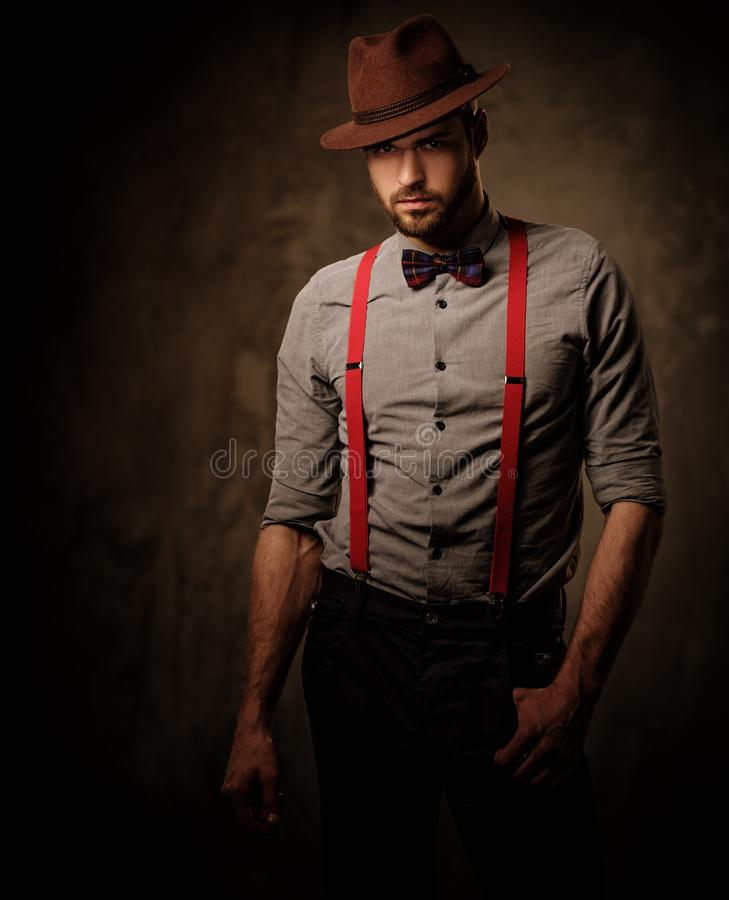 Free Serious Old-fashioned Man With Hat Wearing Suspenders And Bow Tie, Posing On Dark Background. Stock Photo - 70065300