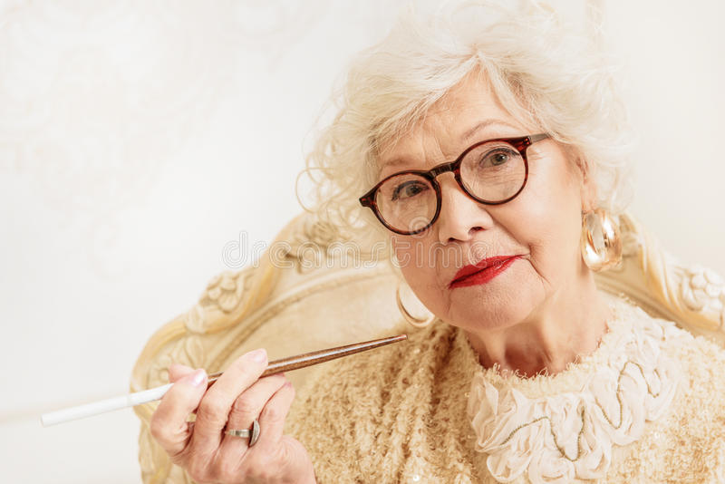 Serious old woman smoking cigarette. Elegant mature lady is holding tobacco pipe. She is sitting on chair and looking at camera with seriousness stock image
