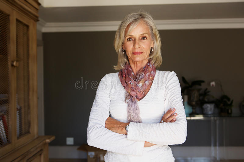 Serious older woman standing in study with arms crossed. Portrait of serious older woman standing in study with arms crossed stock photo