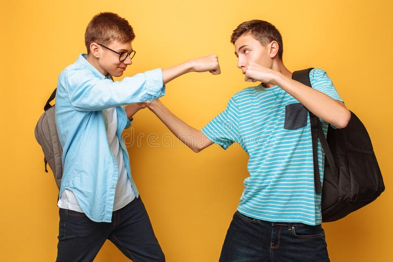 Serious opponents, two teenagers, guys show fists, ready for battle, have strict facial expressions, on a yellow background stock photography