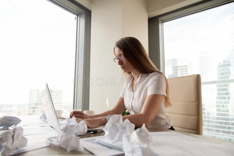 Serious overwhelmed businesswoman working on laptop surrounded b. Serious overwhelmed businesswoman working on laptop after hours to meet deadline surrounded by royalty free stock photos