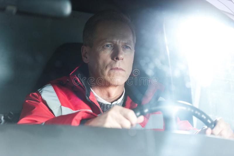 Serious paramedic sitting in ambulance on driver. Seat stock photos