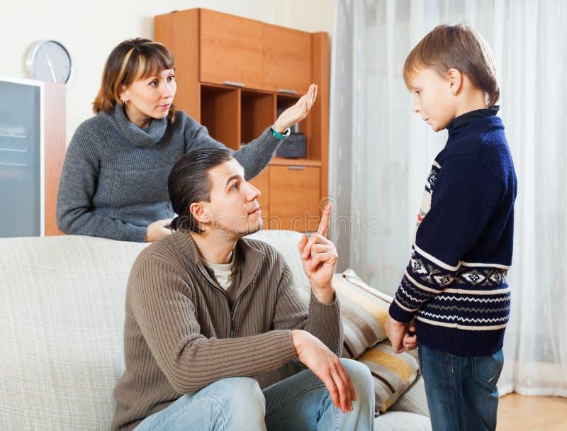 Serious parents berating teenage boy stock image