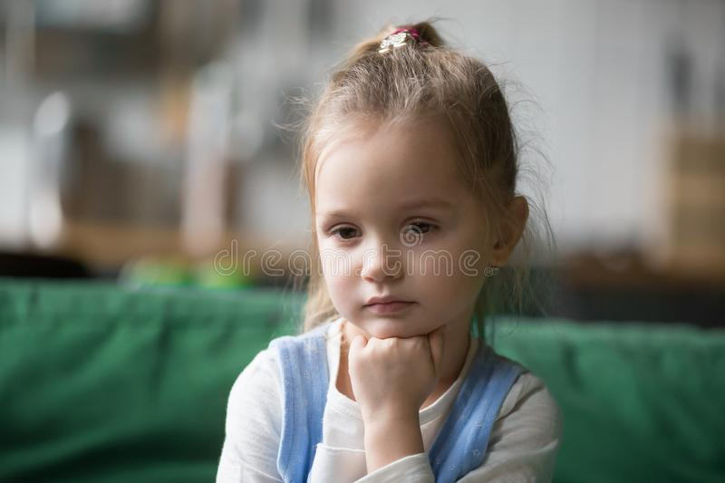 Serious pensive kid girl looking away lost in thoughts concept stock images