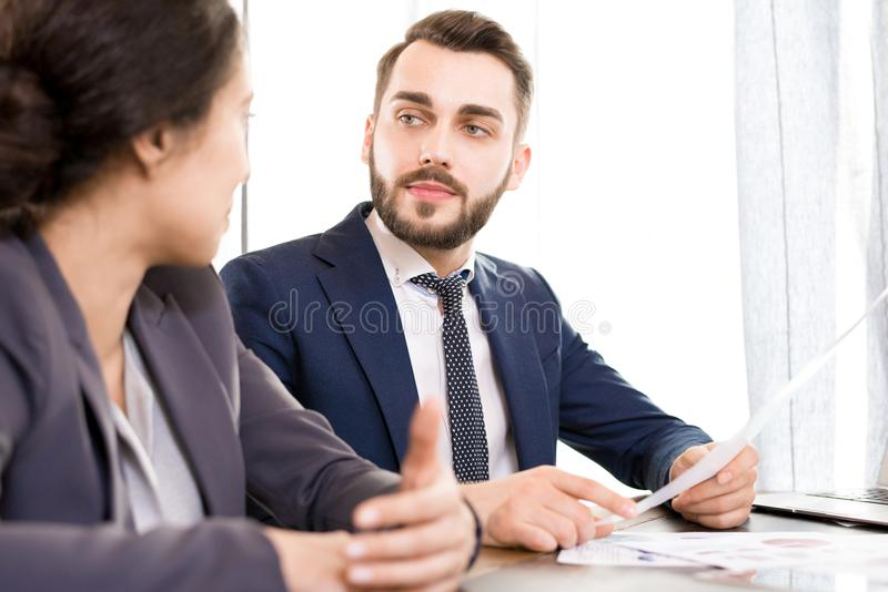 Serious businessman viewing documents with colleague. Serious pensive handsome young businessman with beard and mustache holding paper and looking at colleague royalty free stock photo