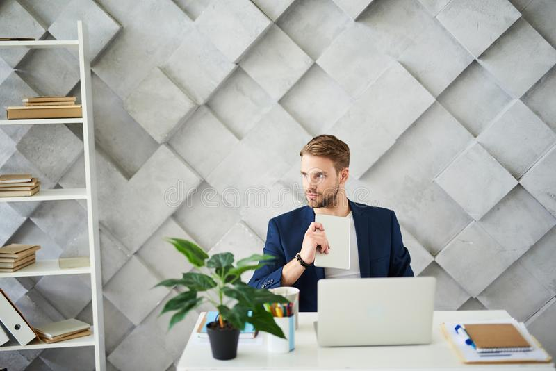 Thoughtful man considering business plan in office royalty free stock image