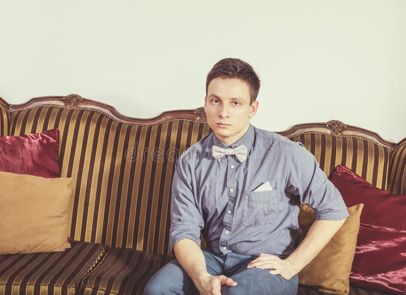 Serious person in shit and bow tie resting on an old retro class. Young man posing seated on a sofa at home. Male model sitting on couch at home. Serious person royalty free stock photo