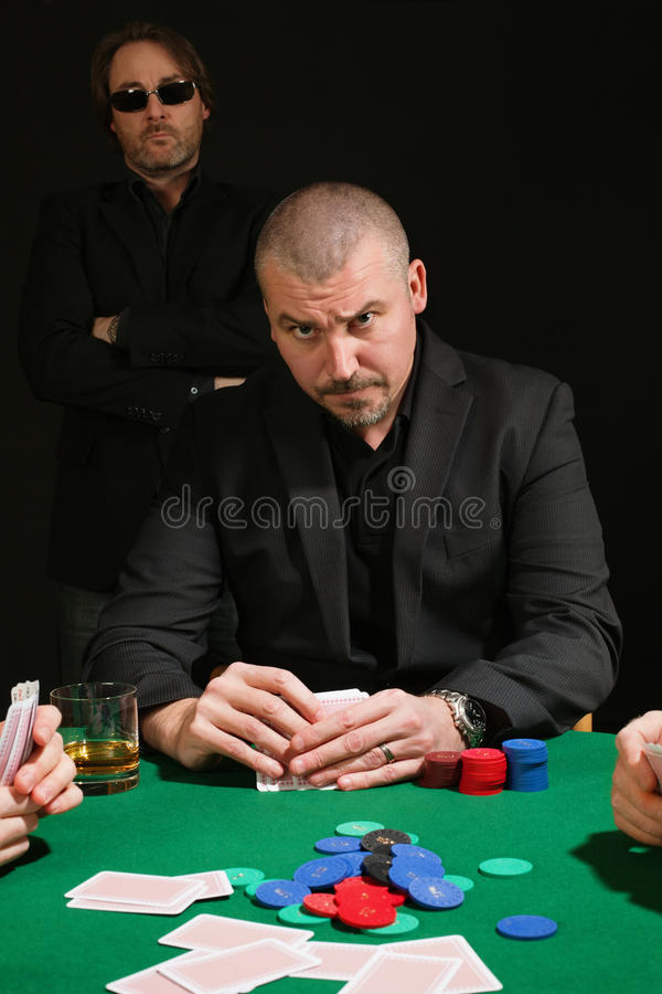 Serious poker player. Photo of a very serious poker player staring across the table. Cards have been altered to be generic royalty free stock photos