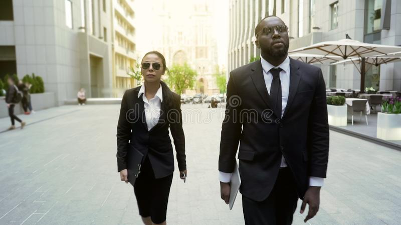 Serious police detectives walking in city downtown, investigators on duty royalty free stock image