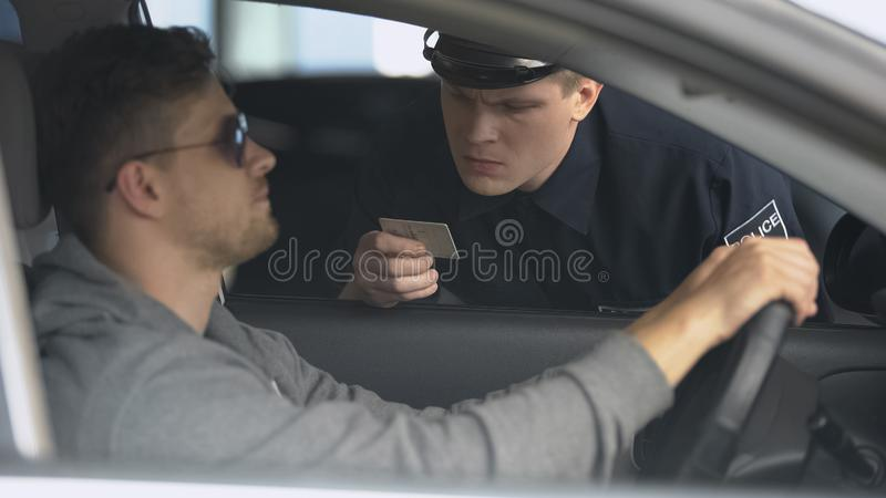 Serious policeman checking male drivers license after exceeding speed limit. Stock photo royalty free stock photography
