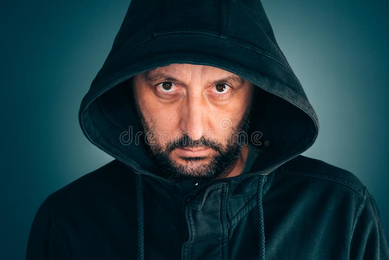 Serious portrait of adult man with hoodie. Looking at camera stock photos