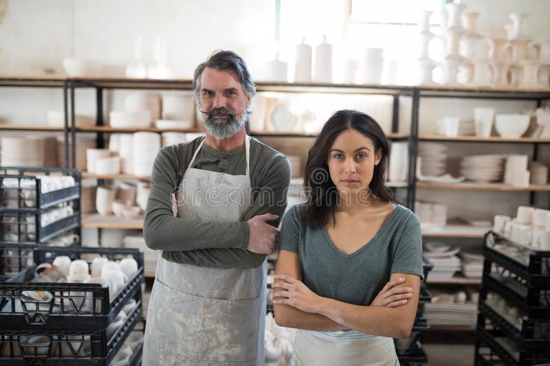 Serious potter colleagues looking at the camera. In the pottery workshop royalty free stock photo