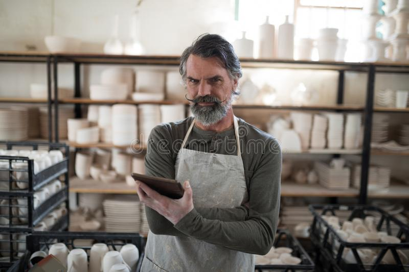 Serious potter using tablet surrounded by work. In the pottery workshop stock photography