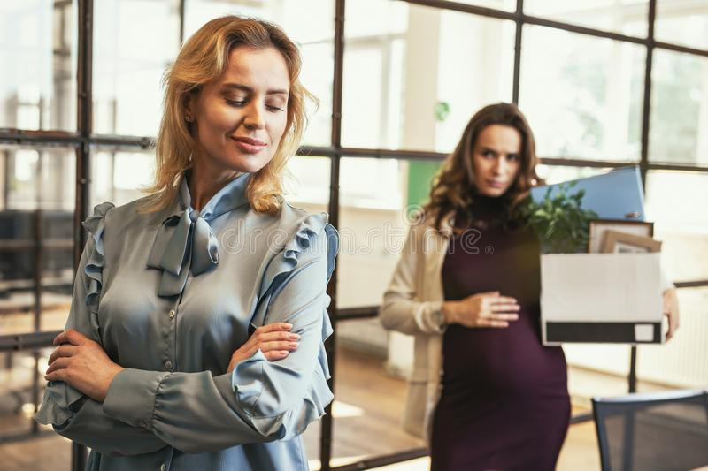 Serious pregnant CEO leaving office royalty free stock image
