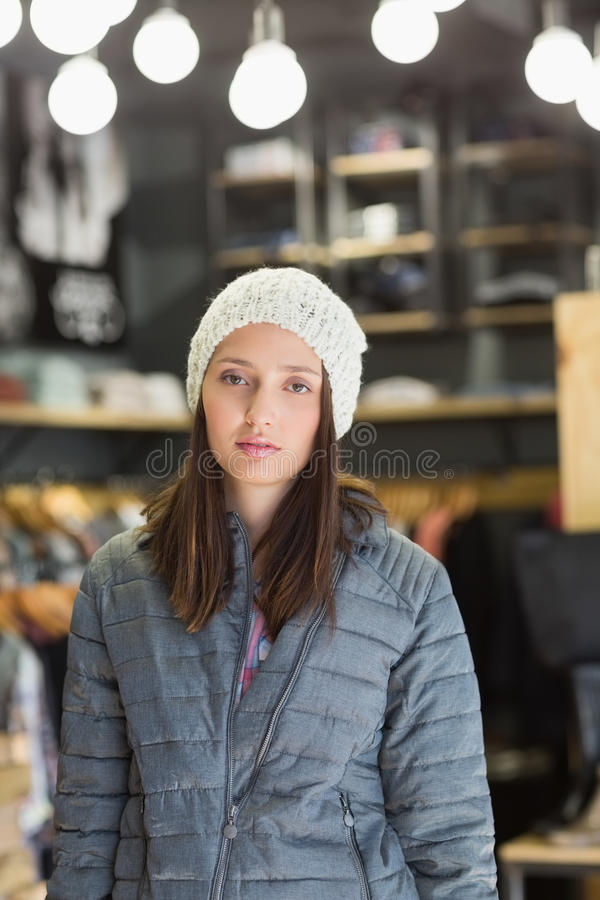 Serious pretty brunette looking at camera with winter clothes stock image