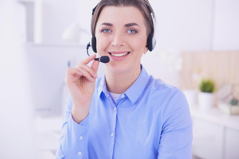 Serious pretty young woman working as support phone operator with headset in office royalty free stock images