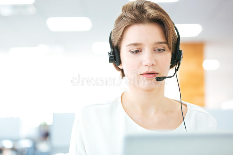 Serious pretty young woman working as support phone operator royalty free stock photography