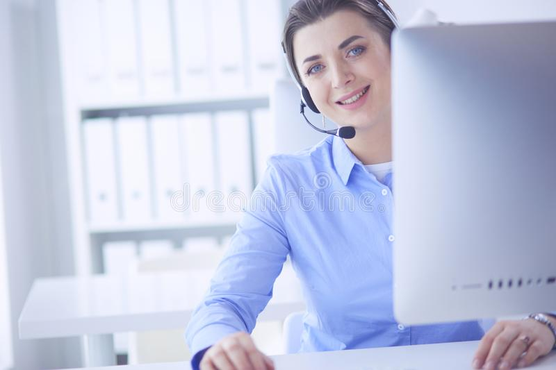 Serious pretty young woman working as support phone operator with headset in office stock photography