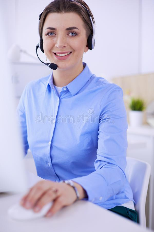 Serious pretty young woman working as support phone operator with headset in office royalty free stock image