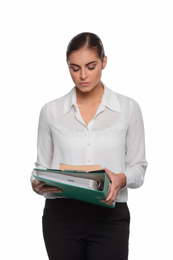 Serious professional with a documentation. In her hands. Businesswoman looks down at the green folder without emotions royalty free stock photos