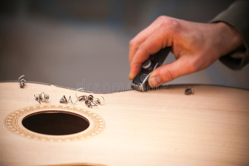 Serious professional guitar-maker working with unfinished guitar at workshop.  royalty free stock photos
