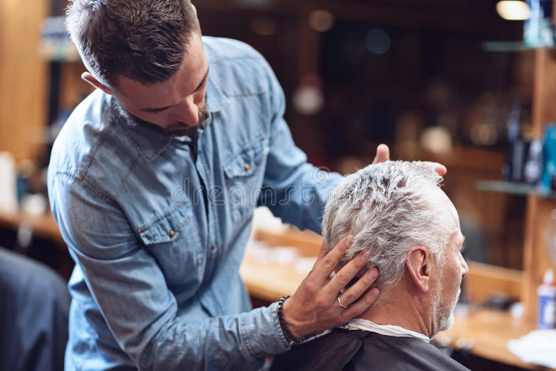 Serious professional hairdresser doing hair styling. Trendy haircut. Serious professional male hairdresser looking at his clients hair and doing hair styling royalty free stock image