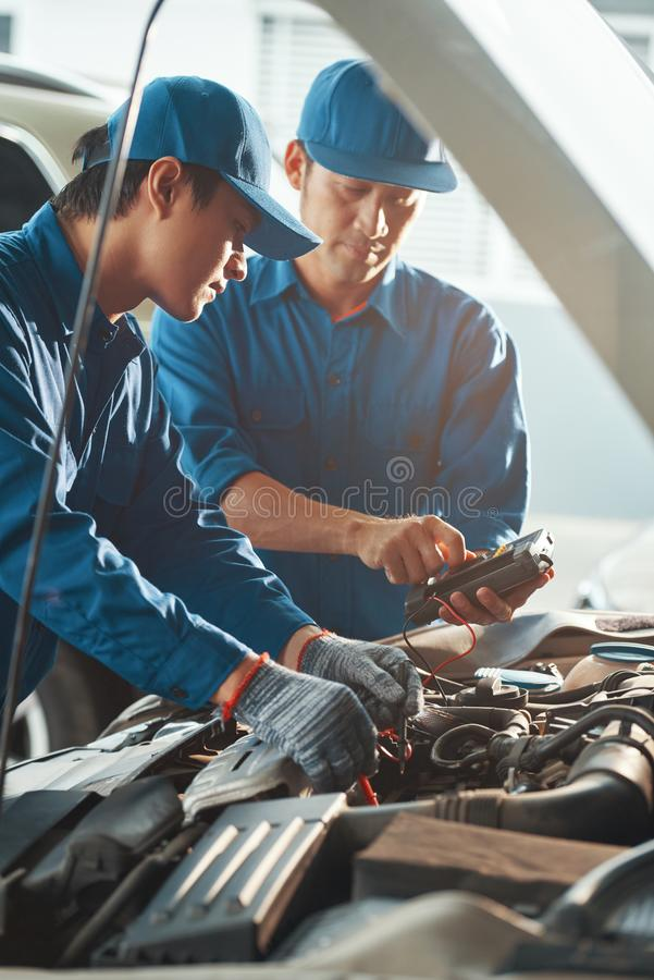 Technicians measuring battery voltage. Serious professional Vietnamese technicians setting multimeter to measure voltage of battery stock photography