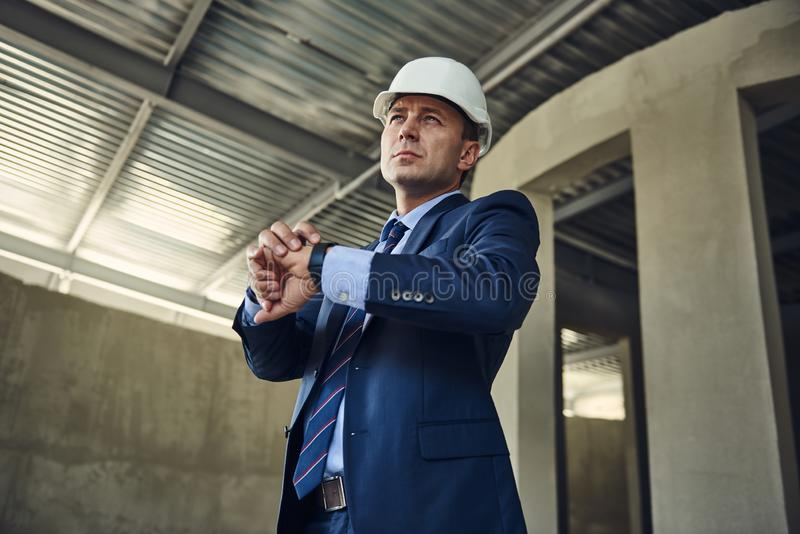 Serious project manager is looking on construction site stock image