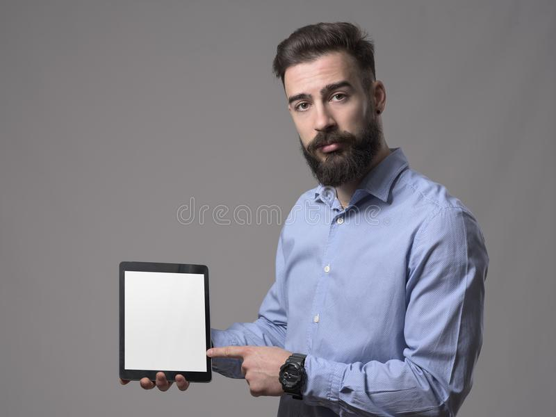 Serious proud and confident successful business man advertising and pointing finger at blank empty tablet screen stock image