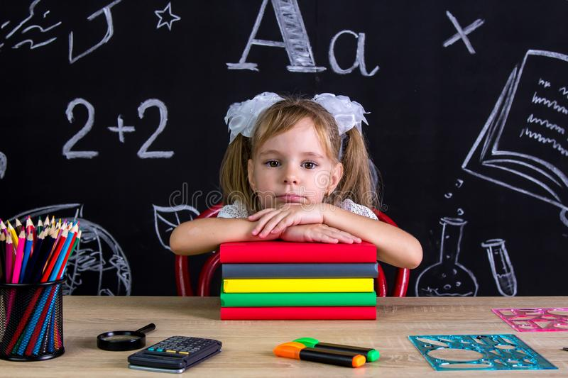 Serious and puzzled schoolgirl sitting at the desk with a pile of books under the chin, surrounded with school supplies royalty free stock images