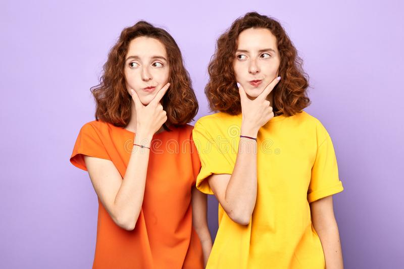 Serious puzzled young twonsisters holds both palms on chin looks away, aside. royalty free stock images