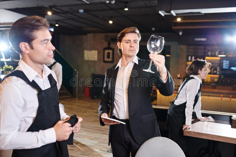 Serious restaurateur examining wineglass cleaned by waiter stock photography