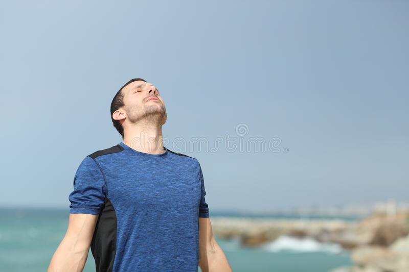 Serious runner breathing fresh air on the beach. Serious runner breathing deeply fresh air on the beach after sport royalty free stock image