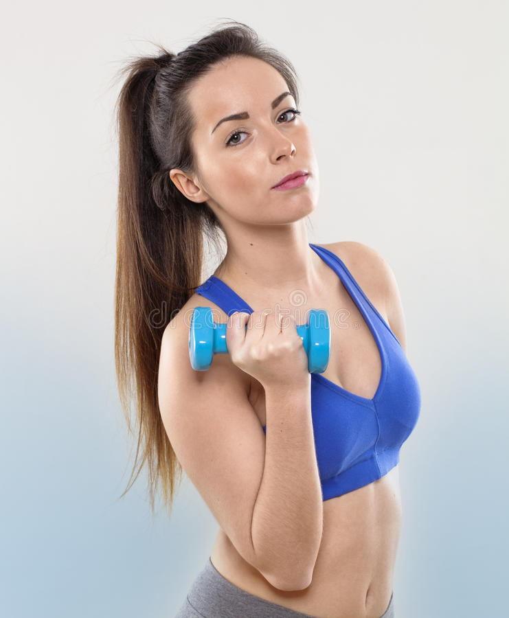 Serious 20s brunette girl exercising with dumb bells for toned arms and body care stock photo