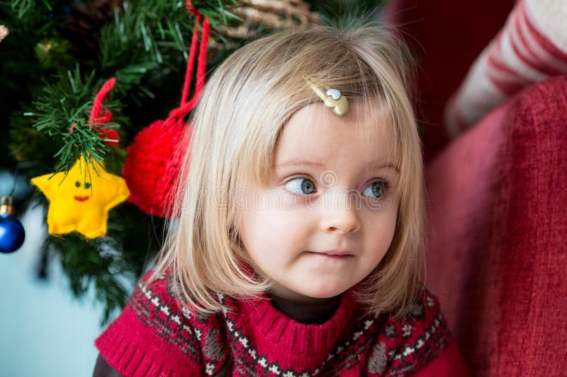 Serious sad or thinking young baby caucasian blonde girl portrait at home near christmas tree royalty free stock images