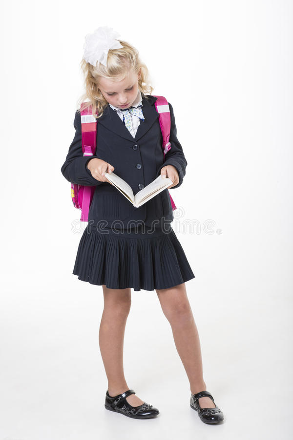 Serious school girl reads a book