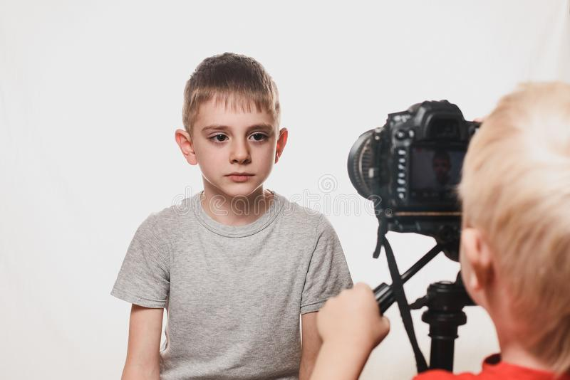 Serious schoolboy giving an interview, the boy with the video camera. Young video blogger. White background royalty free stock photography