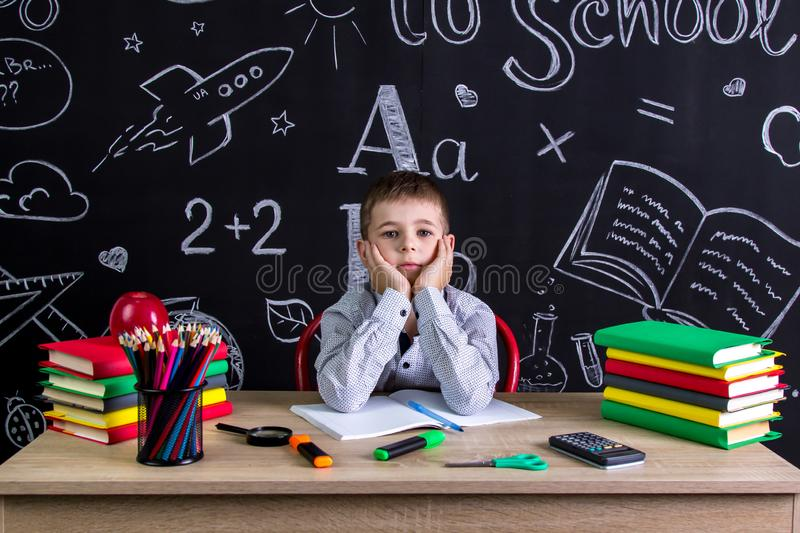 Serious schoolboy sitting on the desk with books, school supplies, with both arms under the cheecks stock images