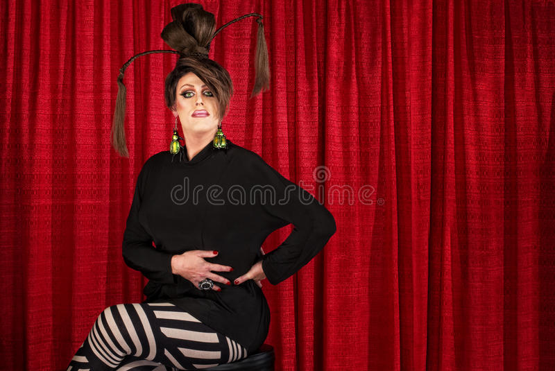 Serious Seated Man in Drag. Serious man in drag seated in front of curtain royalty free stock photos