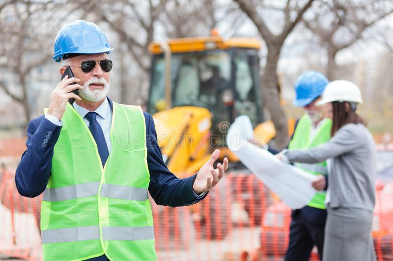 Serious senior architect or businessman talking on the phone while working on a construction site. Senior men and young women looking at blueprints, blurred in royalty free stock photography