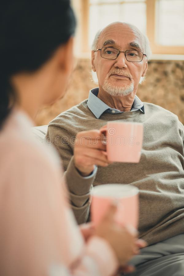 Serious senior in brown sweater carrying cup of coffee. Wise old man. Serious senior in brown sweater carrying cup of coffee staying in nursing home royalty free stock images