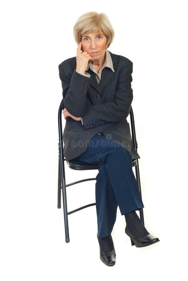 Serious senior business woman on chair stock photo