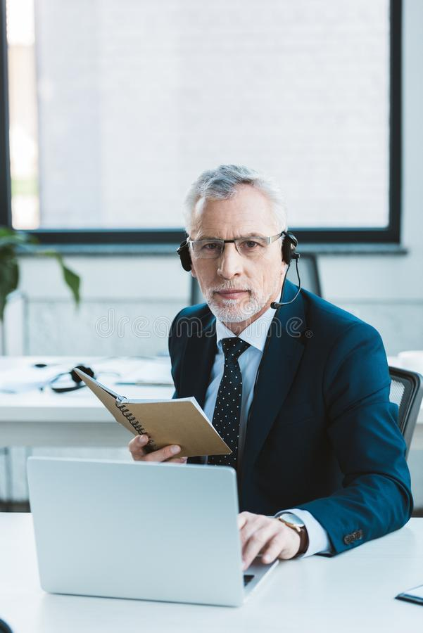 Serious senior businessman in eyeglasses and headset using laptop and looking. At camera stock image